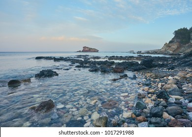 Stones and rocks in forefront with creamy surf ebbing and flowing on Polis beach, Cyprus. Background contains more shoreline and Troodos mountains on horizon.