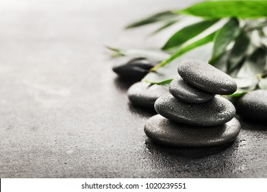 Stones for spa and green leaves on dark background.