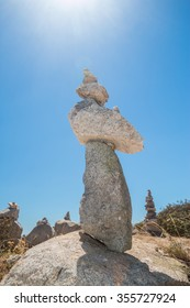 Stones stack against blue sky and sun at the Monte Foia in Monchique, Portugal