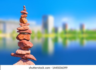 Stones stack balance and blurred office building with green park and blue sky - Property development concept image