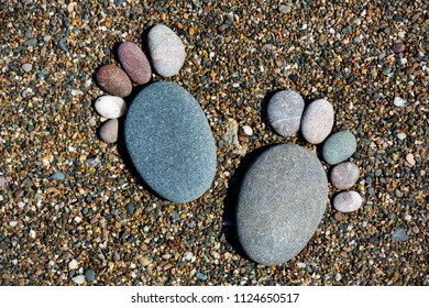 Stones stacked in the form of footprints on small pebbles on the beach