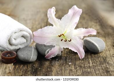 stones, white lilt flower towel, on old wood