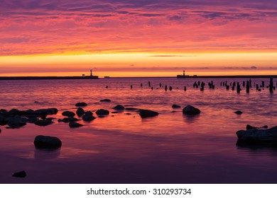 Stones and wooden posts of destroyed jetty while dramatic colorful sunset with low rainy clouds on Baltic sea in Liepaja, Latvia