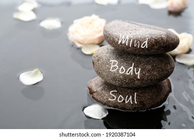 Stones with words Mind, Body, Soul and flower petals in water, space for text. Zen lifestyle