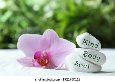 Stones with words Mind, Body, Soul and orchid on sand. Zen lifestyle