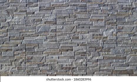 Steinzeug-Fliesen mit Steineffekt für Außenwandverkleidungen. Die Farben sind grau und braun. Hintergrund und Textur