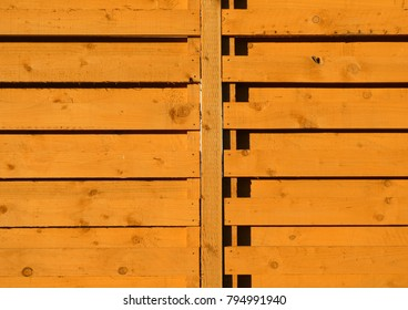 Stong sun shine casts hard shadows on wooden garden fence.