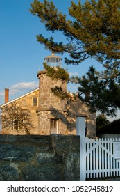 Stonington Harbor lighthouse, an iconic architectual structure, sits behind a stone wall and picket fence in front of evergreen trees in Connecticut.