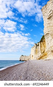 Stony coastline and chalk cliffs in Etretat, Normandy, France. Popular touristic destination