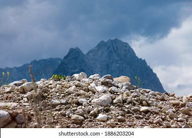 Stony hill with plants in front of a mountain range and storm clouds in the sky.