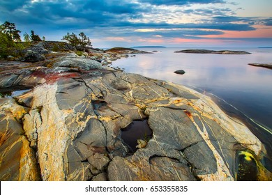 Stony plateau on the shore. Color stone. The stone plays in different colors. Natural stone. Karelia. Ladoga lake.