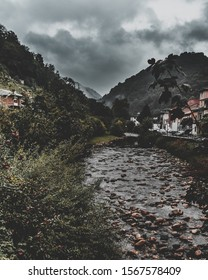 Stony river almost without water between mountains from a bridge with stormy weather. Belmonte de Miranda in Asturias.