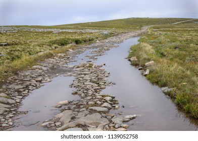 Stony road across the tundra with mud and large puddles