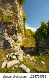 Stony wall falling into peaces, ruins of a former castel of Montousse, France