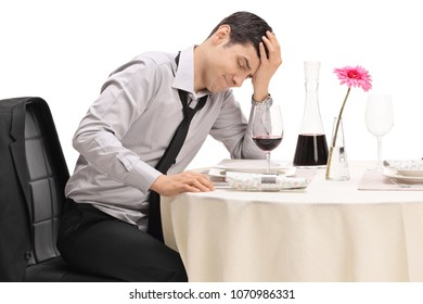 Stood up guy sitting at a restaurant table and holding his head in disbelief isolated on white background