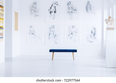 Stool on white floor against wall with drawings in bright art gallery with sculpture