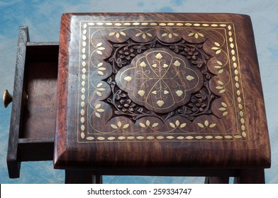 Stool of rosewood inlaid with brass and decorated with carvings.