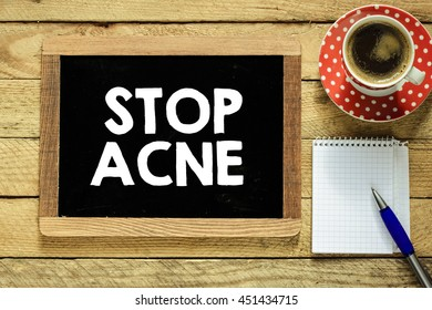 Stop acne on blackboard. Stop acne On blackboard with cup of coffee, notebook and pen on wooden background