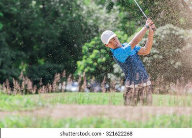 Stop action yong asian golfer after explosion sand bunker.