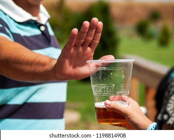 Stop alcohol concept. A man making a stop gesture to a glass of beer