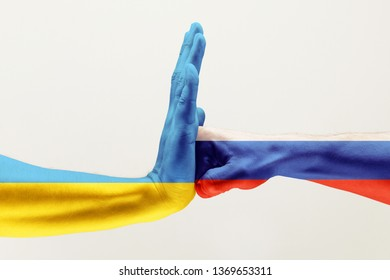 Stop the brother's hit. Two male hands fighting colored in Russian Federation and Ukraine flags isolated on white studio background. Concept of political, economical, social aggressions, disagreement.