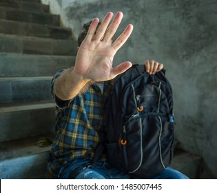 stop bullying abuse and discrimination campaign. young student man with backpack rasing hands covering his face helpless suffering harassment and violence due to sexual orientation