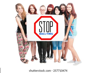 Stop bullying concept written on cardboard held by a bunch of young girl on white background
