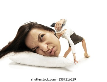 Stop calling me. Big head on small body lying on the pillow. Woman in office suit cannot wake up 'cause headache and overslept. Concept of business, working, hurrying up, time limits, deadline.