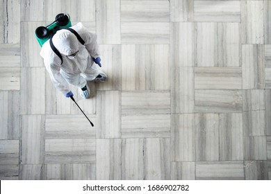 Stop COVID-19. Top view of an unrecognizable person in white chemical protection suit doing disinfection and spraying of public areas to stop highly contagious corona virus. Copy space provided.