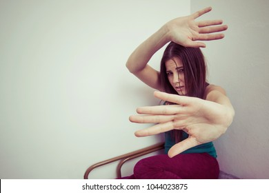 stop domestic violence against woman concept. sad woman looking fearful and helpless stretching hands to defend from violent physical attack by crual man