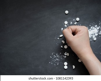 Stop drug addiction concept. Human hands crushing white pills on dark background w/ copy space. International Day against Drug Abuse.