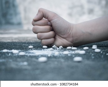 Stop drug addiction concept. Young human hand crushing white pills with fist on grungy concrete floor. International Day against Drug Abuse. Close up.