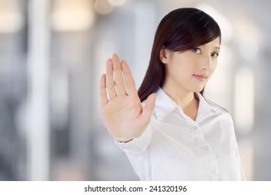 Stop gesture by confident business woman, closeup portrait.