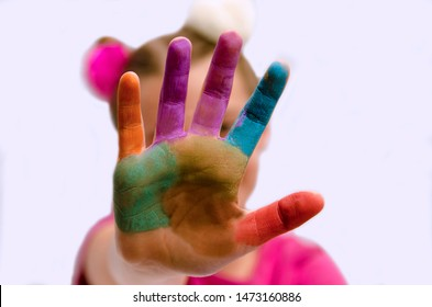 Stop gesture of child colorful palm in front of her head.Close up on little girl painted hand