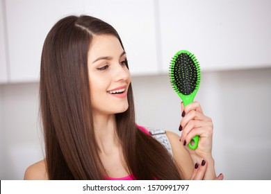 Stop hair loss. Girl holds a hairbrush without hair and smiling. Closeup