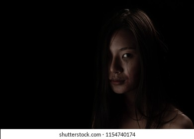 Stop hurting woman! Young beaten up woman looking and stretching out hand while standing against dark wall , Black and white women Painful. Stop violence against children, women and the elderly.