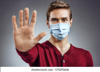 """Stop the infection! Healthy man showing gesture """"stop"""". Photo of man wear protective mask against infectious diseases and flu. Health care concept."""