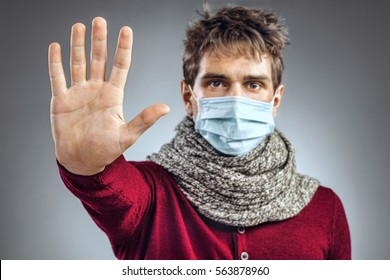Stop the infection! Young man wears protective mask and showing gesture stop. Health care concept