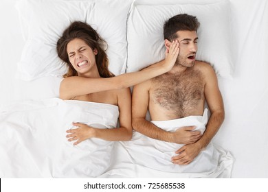 Stop it! High angle view of irritated young woman with painful grimace, clenching teeth and slaping her sleeping husband on face, trying to wake him up and stop annoying disturbing snoring sound