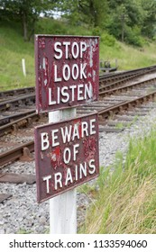 Stop, Look and Listen, and Beware of Trains warning sign on a railway line.