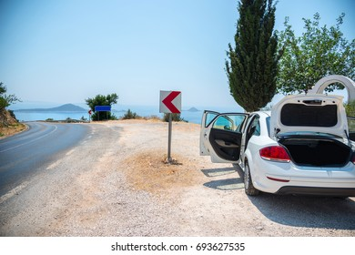 Stop and look to the sea. White car on the roadside of a bend of a mountain road overlooking the sea.