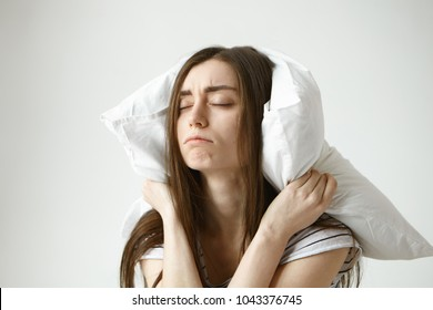 Stop making this annoying sound. Indoor shot of frustrated upset young woman with messy hair suffering from insomnia or some sleeping disorder, can't relax because of irritating dripping water sound