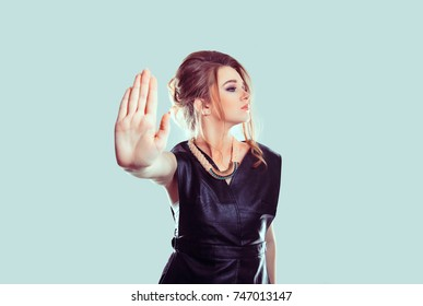 Stop, no. Closeup portrait young annoyed angry woman giving talk to hand gesture with palm outward isolated light blue wall background. Negative human emotion face expression feeling body language