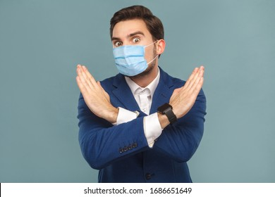 Stop, no! Portrait of young man with surgical medical mask standing. showing hand ban close at camera. Business people medicine and health care concept. Indoor, studio shot on blue background