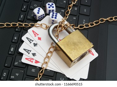 Stop online gambling concept with padlock, playing cards and laptop keyboard