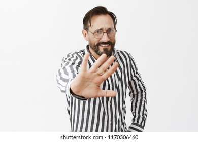 Stop photographing me. Portrait of nervous displeased boss being caught for embezzlement, pulling hands towards camera to ask stop shooting him, standing anxious and unhappy over gray background