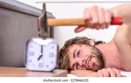 Stop ringing. Annoying ringing alarm clock. Man bearded annoyed sleepy face lay pillow near alarm clock. Guy knocking with hammer alarm clock ringing. Break discipline regime. Annoying sound.