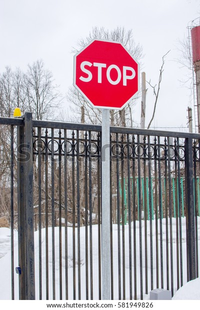 Stop road sign near the iron fence. Winter landscape behind