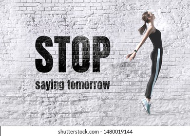 Stop saying tomorrow - inspirational motivational quote in the form of graffiti on the background of an old white brick wall. Comely slim young energetic woman engaged in fitness