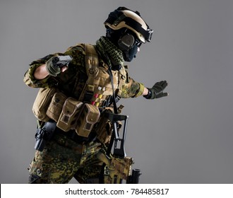 Stop. Side view severe soldier holding gun while gesticulating arm. Ammunition concept. Isolated amd copy space